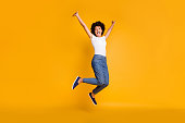 Full length body size side profile photo jumping high beautiful she her lady hands arms up win game play match wearing casual jeans denim white t-shirt clothes isolated yellow bright vivid background.