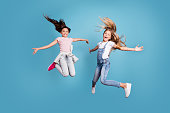 Full length body size view of two people nice lovely attractive cheerful straight-haired pre-teen girls having fun day daydream yes goal achievement free time isolated on blue background.