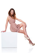 Full length fashion model in gorgeous pale rose color dress posing sitting at white cube, over white background