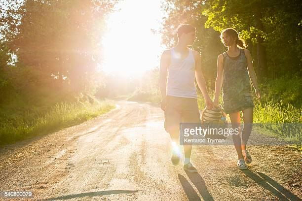 Full length front view of couple walking on dirt road against bright sun