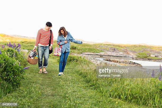 Full length front view of couple walking on field