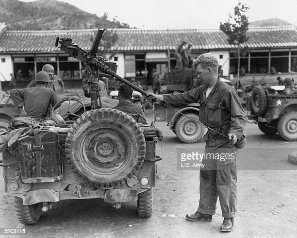 Full length image of United States Army Corporal Clifford B Nash of Howland Maine cleaning a 50 caliber machine gun mounted on the rear of a jeep in...
