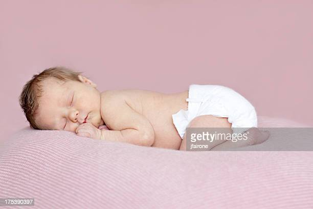 Full length newborn baby girl asleep on tummy. Pink background.