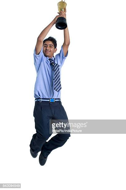 Full length of a boy jumping in air with trophy against white background