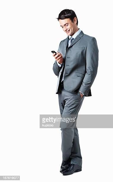 Full length of a businessman text messaging on cellphone
