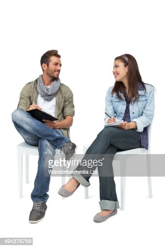 Cool young couple writing in notepads : Stock Photo