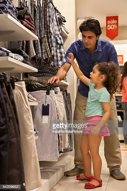 Full length of a man with his daughter choosing clothes in shopping mall
