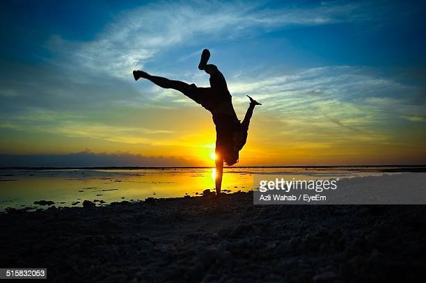 Full Length Of A Silhouette Man Jumping On Beach