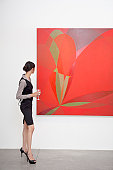 Full length of a woman looking at painting in art gallery