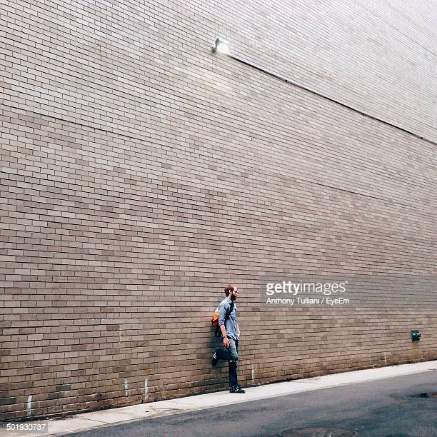 Full length of a young man standing against brick wall