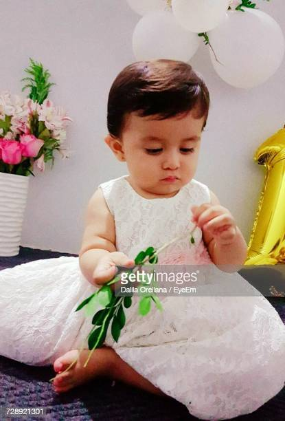 Full Length Of Baby Girl Holding Leaves On Carpet At Home