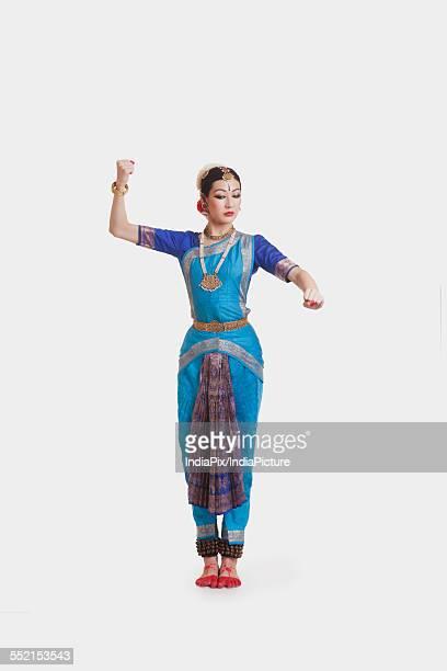 Full length of beautiful dancer performing Bharatanatyam against white background