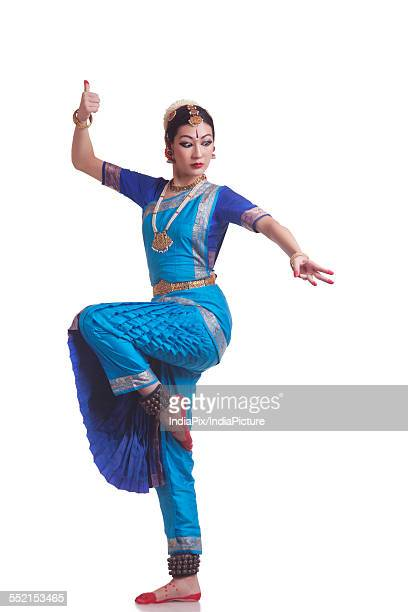 Full length of Bharatanatyam classical dancer performing over white background