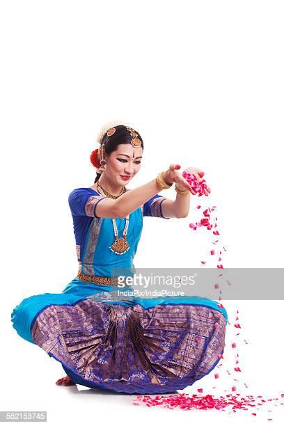 Full length of Bharatanatyam dancer dropping rose petals over white background