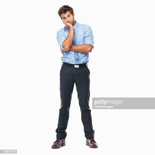 Full length of bored business man standing with hand on face against white background