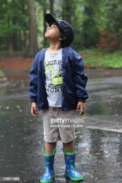 Full Length Of Boy In Raincoat Looking Up While Standing On Road During Rainy Season