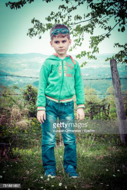 Full Length Of Boy Looking Away While Standing On Grassy Field