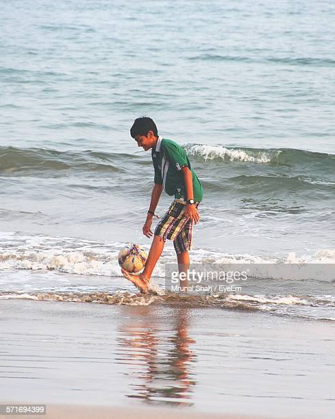 Full Length Of Boy With Soccer Ball On Beach