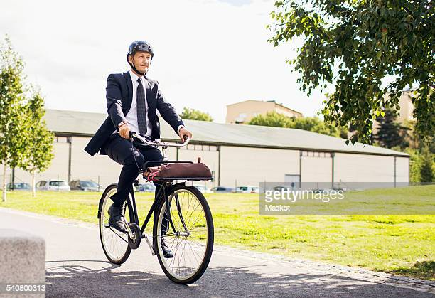 Full length of businessman riding bicycle on street against sky