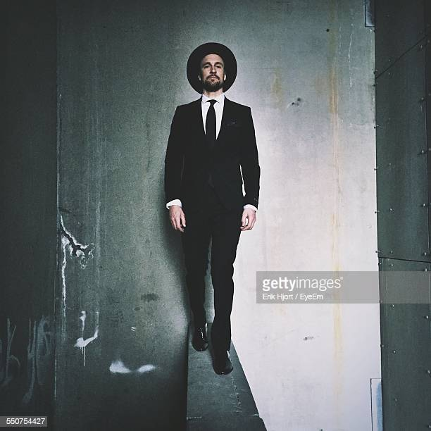 Full Length Of Businessman Walking On Retaining Wall In Building