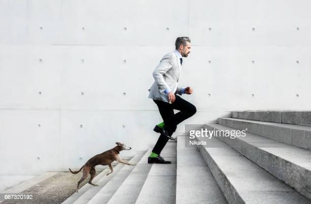 Full length of businessmen running on steps with dog