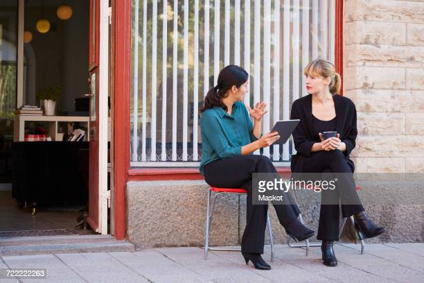 Full length of businesswoman discussing with female colleague outside office