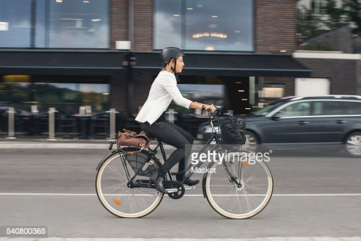 Full length of businesswoman riding bicycle on city street