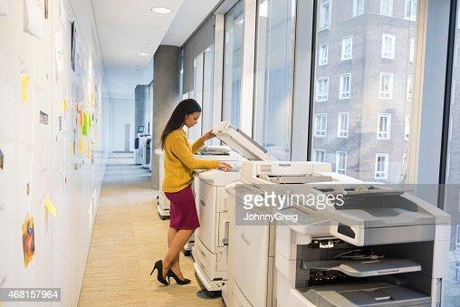 Full length of businesswoman using computer printer