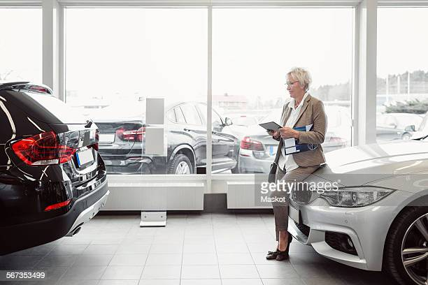 Full length of businesswoman with digital tablet sitting on car at store