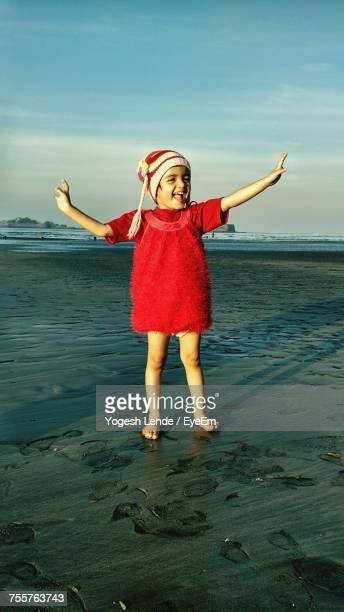 Full Length Of Cheerful Girl Standing At Beach Against Sky During Sunset