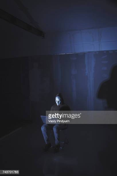 Full length of computer hacker wearing mask using laptop while sitting against wall
