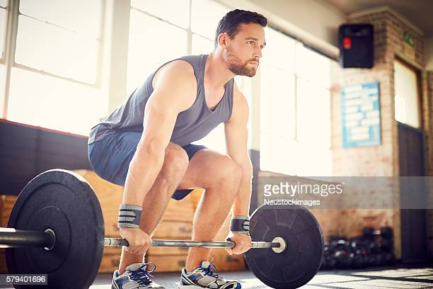 Full length of confident man deadlifting with barbell in gym