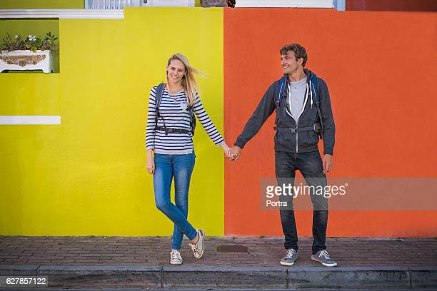 Full length of couple holding hands against wall