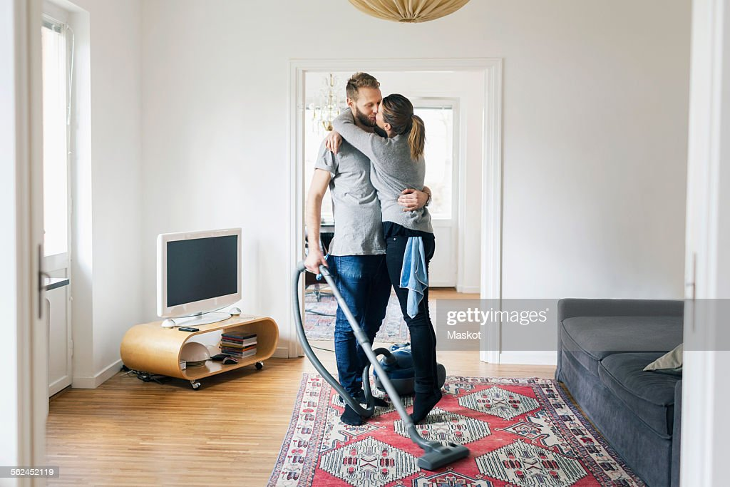 Full length of couple kissing while cleaning home
