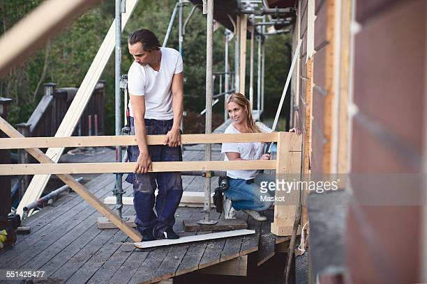 Full length of couple working on porch of house being renovated