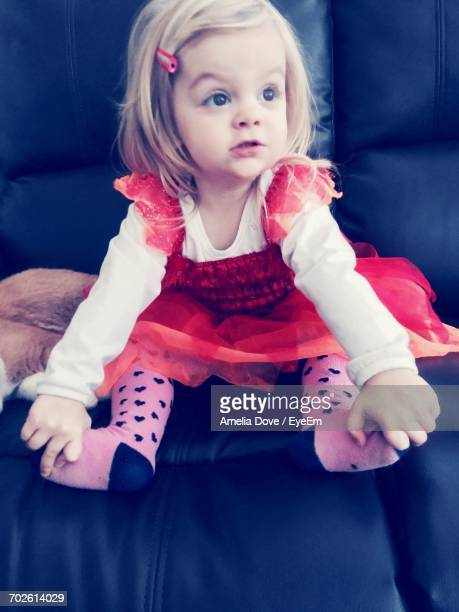 Full Length Of Cute Girl Sitting On Sofa At Home