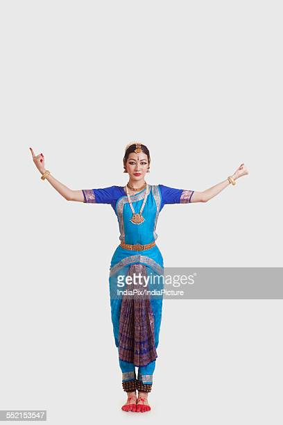 Full length of dancer in traditional wear performing Bharatanatyam against white background