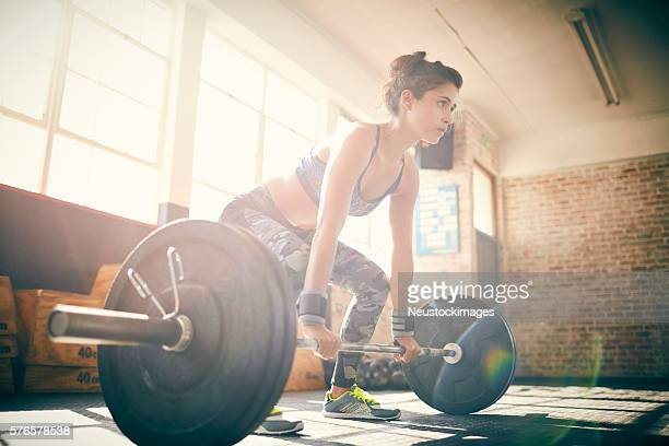 Full length of determined young female deadlifting barbell in gy