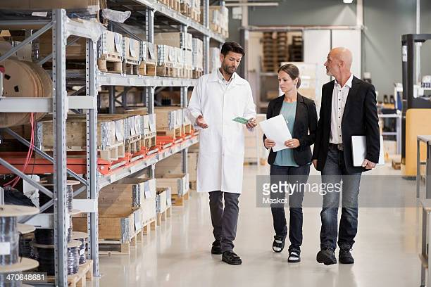 Full length of engineer explaining machine part to business people in factory