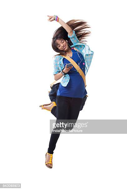 Full length of excited young woman enjoying music over white background