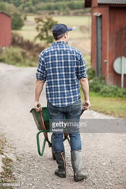 Full length of farmer pushing wheelbarrow on rural road
