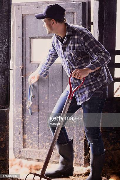 Full length of farmer with pitchfork closing barn door