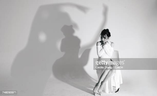 Full Length Of Fashion Model Sitting On Chair Against Shadow On White Background