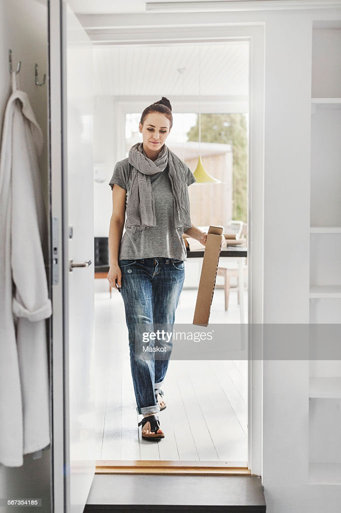 Full length of female architect walking towards doorway at home