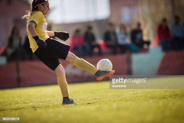 Full length of female goalkeeper kicking soccer ball on playing field.