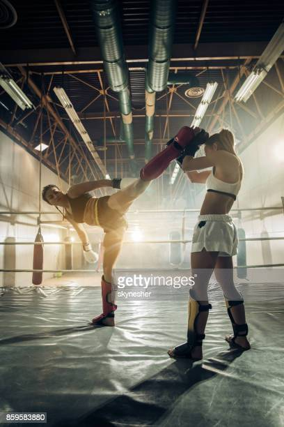 Full length of female kick boxers in a ring during sports training.