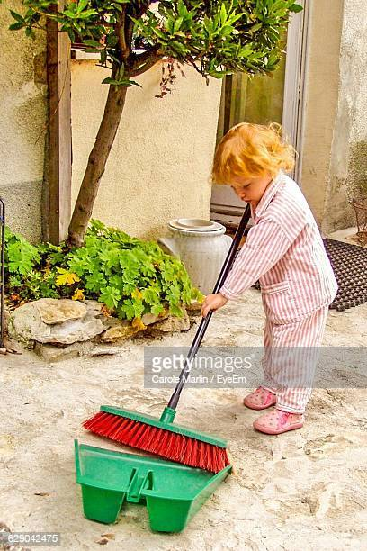 Full Length Of Girl Cleaning Yard With Broom