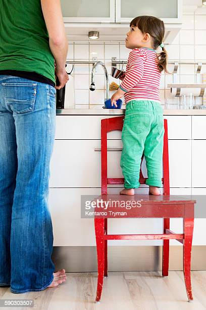 Full length of girl looking at mother while standing on chair in kitchen