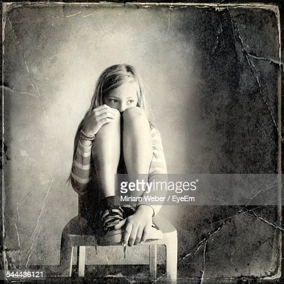 Full Length Of Girl Looking Away While Sitting On Chair At Home