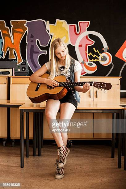 Full length of girl playing guitar while leaning on desk in school
